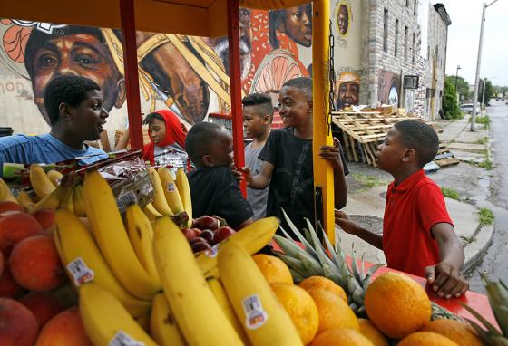 Boys gather around a horse-drawn cart full of produce outside an arabber stable in Baltimore, Maryland. (AP)