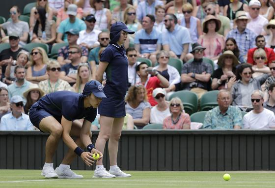 A ball boy and ball girl collect the new balls in a men's singles match at this year's Wimbledon Tennis Championships in London, England. (AP)