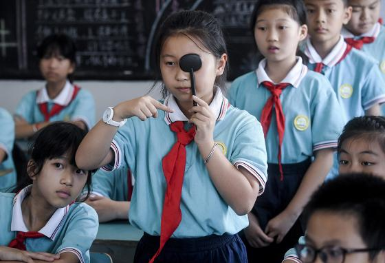 Students line up to get eyesight tests at a primary school in Huzhou City, China. (AP)
