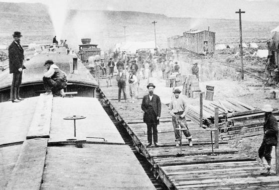 Workers laying tracks for Central Pacific Railroad at camp
