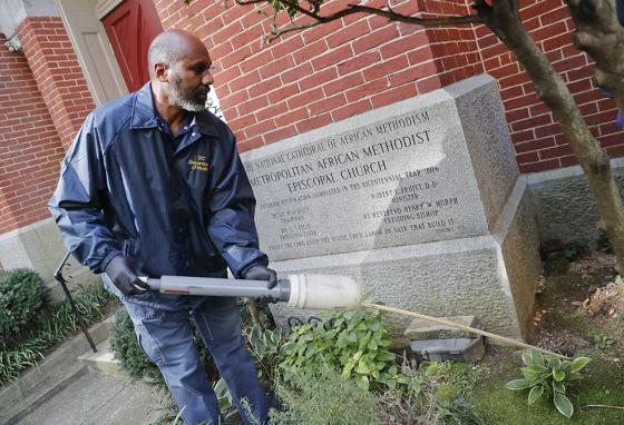 Pest Control officer Gregory Cornes uses a duster to pump poison into rat burrows in Washington, D.C. (AP)