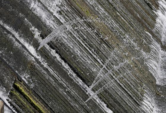 Water spurts through a wood section of a spill gate on Lake McQueeney in Texas. (AP)