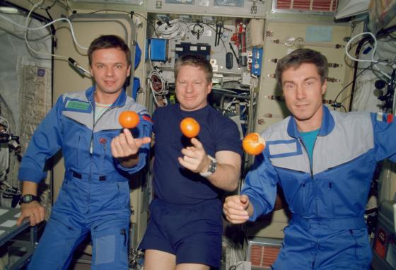 The first astronauts to live on the International Space Station pose with fresh oranges on December 4, 2000. Pictured from left are Yuri Gidzenko, Bill Shepherd, and Sergei Krikalev. (NASA via AP)