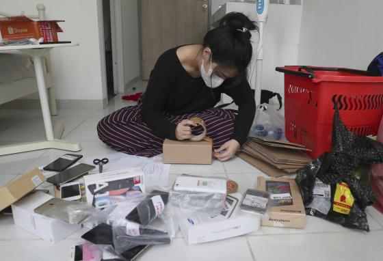 Indonesian journalist Ghina Ghaliya packs used mobile phones. She ships them to children who lack internet access for studying online. (AP)