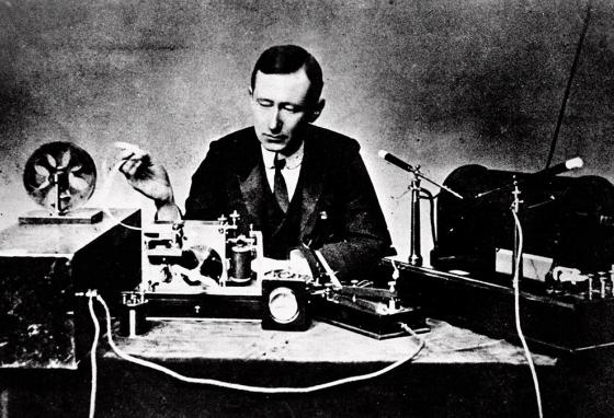 Italian physicist Guglielmo Marconi, who developed the wireless telegraph, reads signals from a spark coil used for ship-to-shore radio tests in 1901.  (AP)