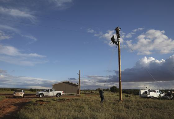 In Arizona, volunteer utility workers prepare a power pole to connect the Haskie home on the Navajo Nation to the electric grid. (AP)