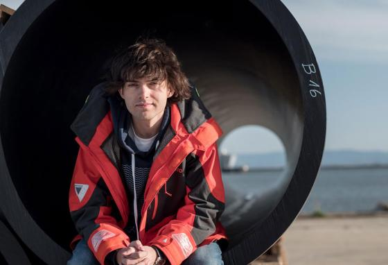 Boyan Slat sits inside a four-foot diameter section of tubing. The tubing is part of an enormous, plastic-trapping, floating boom system. (Ocean Cleanup)
