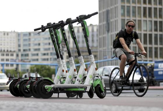 A cyclist rides past electric scooters parked in a public square in Berlin, Germany. Are scooters becoming more popular than bikes? (AP)
