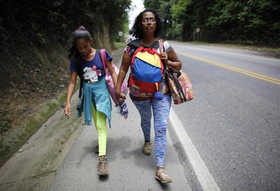 Venezuelan Sandra Cadiz holds the hand of her 10-year-old daughter Angelis as they walk through Colombia on their way to Peru. (AP)