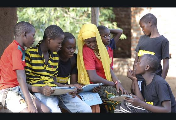 Children in a village in the Tanga region of Tanzania gather to learn from tablets. They're using software that's easy to download for illiterate children. (AP)