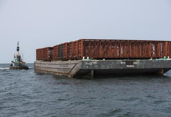 Old rail cars sit on a barge before being dumped into the ocean off the New York coast. The debris will create an artificial reef that will attract marine life. (Darren McGee/Office of Governor Andrew M. Cuomo via AP)