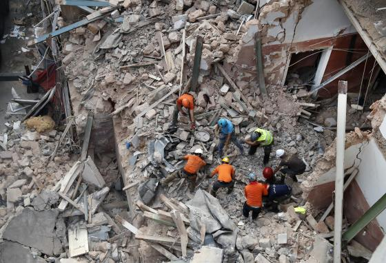 Rescuers search in the rubble of a collapsed building in Beirut after getting signals there may be a survivor nearby. (AP)
