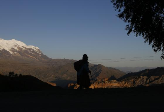 A woman walks a path overlooking the snow-capped Illimani Mountain near La Paz, Bolivia. The Illimani is part of the Andes range. (AP/Juan Karita)