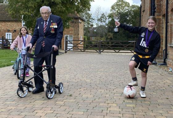 Captain Tom Moore poses for a photo with fellow fundraisers Imogen Papworth-Heidel, right, and Pepa Lorente at his home in Marston Moretaine, England. (Karl Papworth-Heidel via AP)
