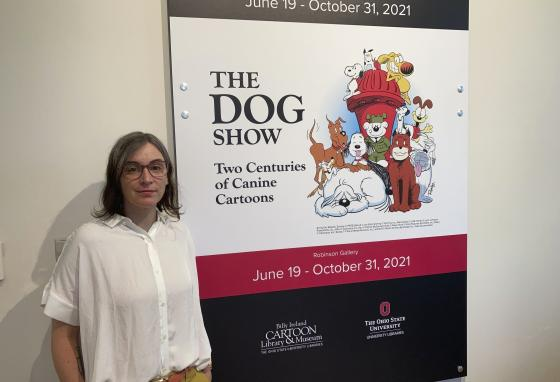 """Anne Drozd stands near Ohio State University's new exhibit, """"The Dog Show,"""" in Columbus, Ohio. She is the museum coordinator at the Billy Ireland Cartoon Library Museum there. (AP/Andrew Welsh-Huggins)"""