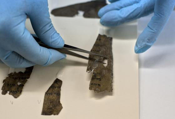 A worker examines fragments of the Dead Sea Scrolls at the Israel Museum in Jerusalem. (AP)