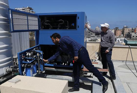 Engineers check the Watergen machine on the roof of the Al-Rantisi Medical Center in Gaza City in the Gaza Strip. (AP)