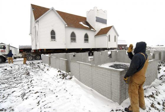 Rob Trenary signals that the alignment is just right as the former Calvary Presbyterian Church arrives at its new site near Barnum, Iowa. (AP/The Messenger, Hans Madsen)