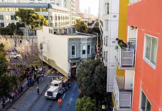 A man watches from a balcony as a truck pulls a Victorian home through San Francisco. (AP/Noah Berger)