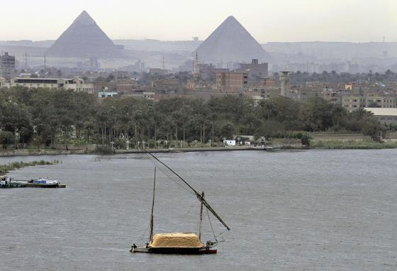 A traditional boat carries a cargo of hay on the Nile River as it sails past the Pyramids of Giza in Cairo, Egypt. (AP)