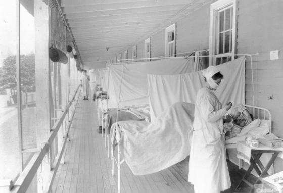 A nurse takes the pulse of a patient in the influenza ward of the Walter Reed military hospital in November 1918. (Harris & Ewing/Library of Congress/AP)