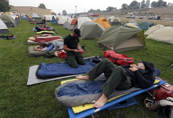 Firefighters rest at their camp. The coronavirus outbreak is making the U.S. Forest Service change strategies for fighting wildfires. (AP)
