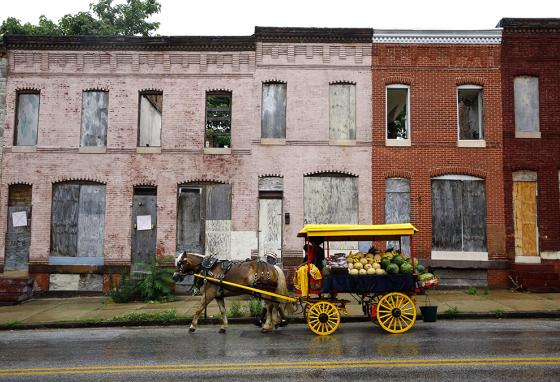 An arabber leads a horse-drawn cart full of produce past abandoned houses. (AP)