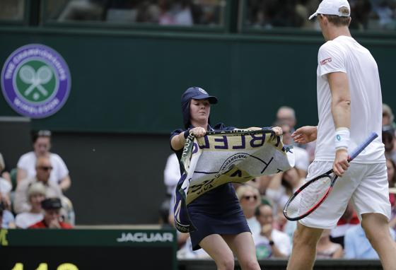 A ball girl hands a towel to South Africa's Kevin Anderson during a men's singles match at Wimbledon. (AP)