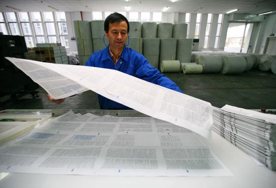 A Chinese worker checks uncut pages of Bibles. (AP)