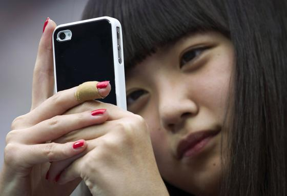 A Chinese girl uses a mobile phone in Beijing, China. (AP)