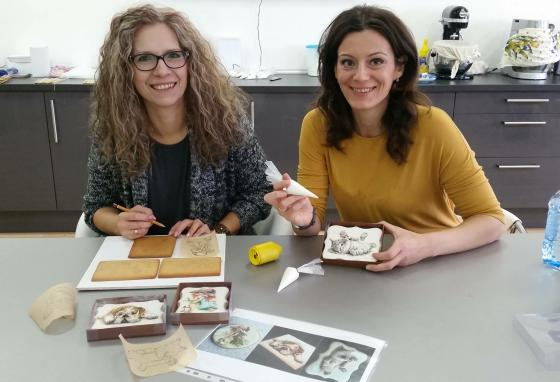 Ms. PoÓr (left) usually works alone. But sometimes, she teaches cookie decorating to others at her workshop. (Mézesmanna)