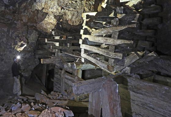 Jeremy MacLee looks at old support timbers in a mine near Eureka, Utah. (AP)