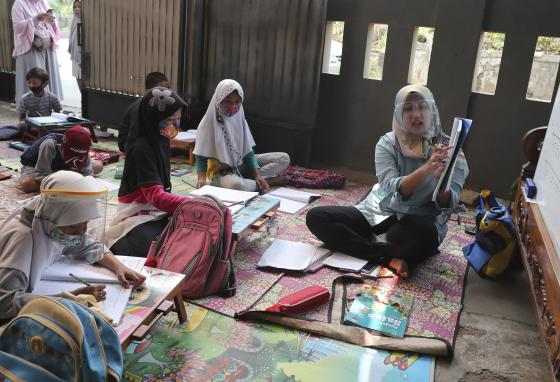 Indonesian teacher Inggit Andini, right, teaches at a makeshift class for students who do not have a way to study online. (AP)