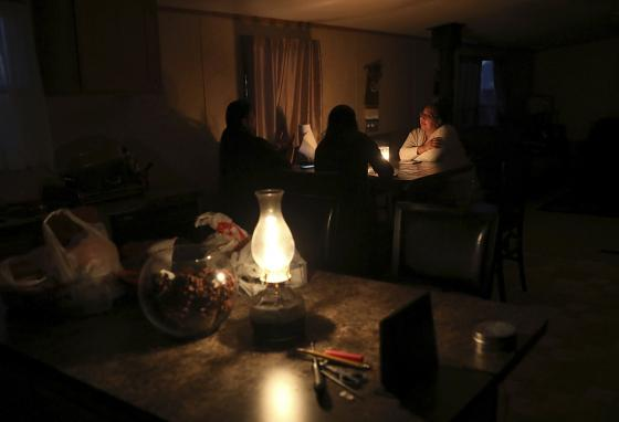 By lamplight, Miranda Haskie talks about living for more than 10 years without being connected to power lines on the Navajo reservation. (AP)