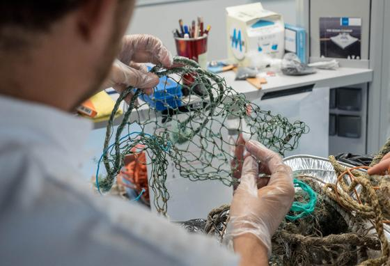 A researcher examines a piece of fishing net. Forty-six percent of the Pacific Garbage Patch is old fishing gear. (Ocean Cleanup)