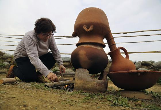 Ms. Lazarou tends to a fire boiling perfume inside a replica 2nd millennium B.C. distiller. (AP)