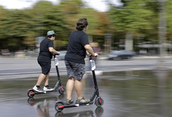 Young people ride on scooters in Paris, France. The city is making rules about where the electric two-wheelers are allowed. (AP)