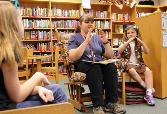 "A children's librarian and a student use sign language while reading ""Are You My Mommy?"" in West Virginia. (AP)"