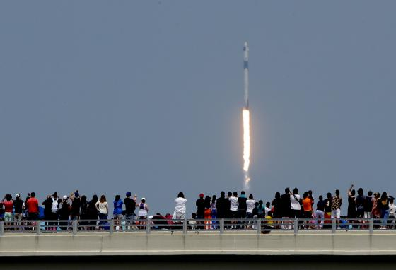 Spectators watch from a bridge as SpaceX Falcon 9 lifts off from the Kennedy Space Center in Florida. (AP)