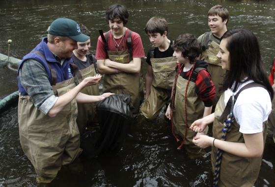Conservation worker Chris Bowser, left, along with some high school students, checks a net for American eels on the Black Creek in West Park, New York. (AP/Mike Groll)