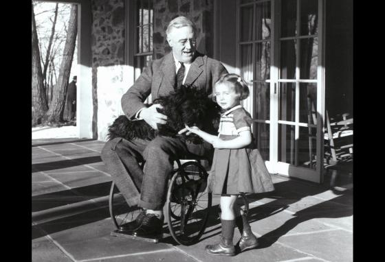 President Roosevelt and friend Ruthie Bie pet his dog Fala in Hyde Park, New York.