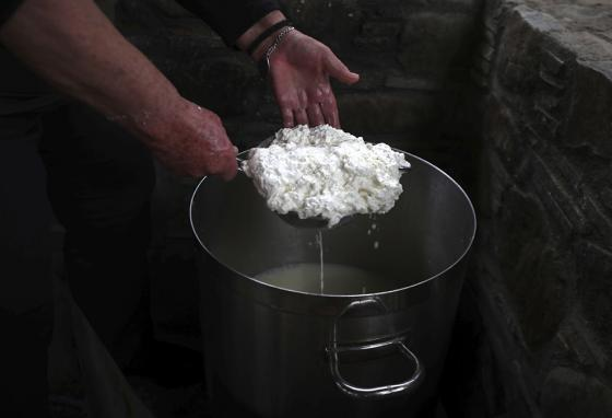 The goat's milk is boiled to make these cheese curds, which are lifted from a saucepan. (AP)