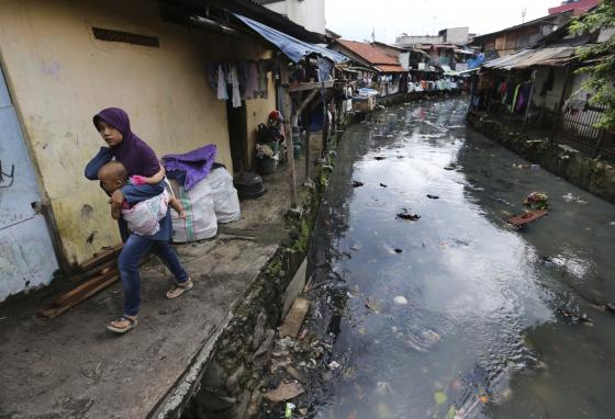 A woman carrying a child walks along a river at a slum in Jakarta, Indonesia. Jakarta has a very dense population. Many people live in slums like this one. (AP)