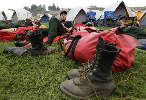 The firefighters slept out in the open because they had to move to a different camp in a few days. (AP)