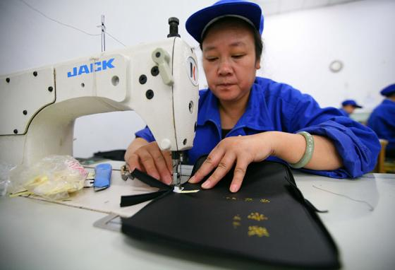 In Nanjing, China, a worker stitches Bibles. (AP)