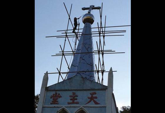 A government worker uses a torch to cut a cross from atop a church in eastern China. (AP)