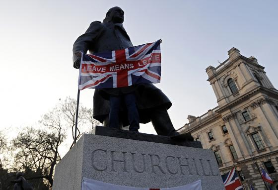 "A demonstrator in favor of Brexit holds a British flag reading ""Leave Means Leave"" in front of the Winston Churchill statue in London. (AP)"
