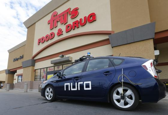 A self-driving Nuro vehicle parks outside a supermarket. A person will ride along during the first part of testing driverless delivery. (AP)