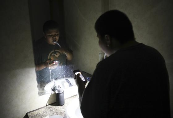 Jayden Long, 13, brushes his teeth by cell phone light in the bathroom of his home on the Navajo reservation. (AP)