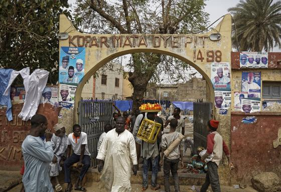 Nigerians walk through the busy entry gate to the ancient dye pits of Kofar Mata in northern Nigeria. (AP)